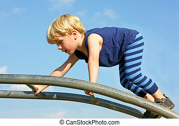 Child Climbing Ladder at Playground - A cute little boy is...