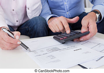 Close-up of couple doing finances at home - Close-up of...
