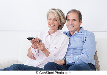 Mature Couple Watching Television - Happy Mature Couple...