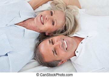 Happy Couple Lying On Bed - Portrait Of Happy Senior Couple...