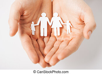 man with family of paper men - man hands showing family of...