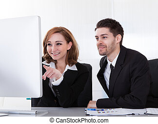 Two business partners looking at computer - Two happy...