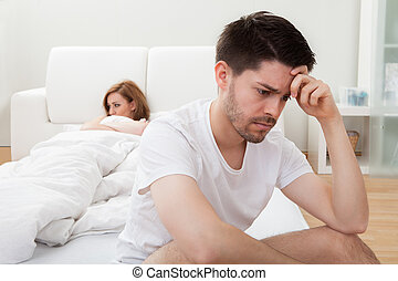 Depressed man sitting on the edge of the bed in bedroom