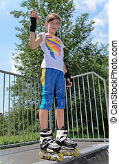 Pretty young teenage roller skater standing on top of a ramp...