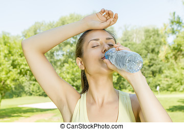 Fitness girl drinking water in the park.