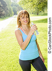 Happy woman drinking water while working out - Smiling...