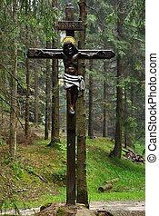 Old religious cross in deep forest after rain
