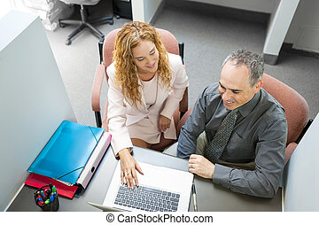 Coworkers looking at computer in office - Man and woman...