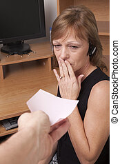 shocked at pink slip - Woman showing surprise at getting a...