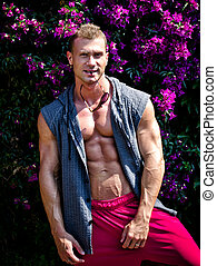 Handsome young muscle man smiling, outdoors, with open shirt...