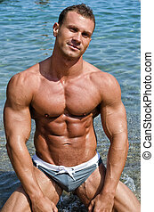 Smiling, muscular young bodybuilder shirtless in the sea -...