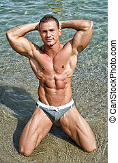 Attractive and fit young bodybuilder in bathing suit...