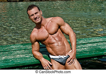 Handsome young bodybuilder leaning on wood planks, smiling -...