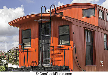 Caboose - Large red caboose train car from a side angle.
