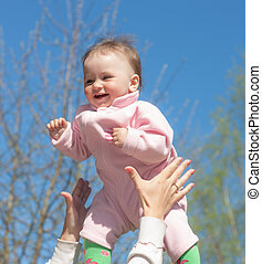 joyfulness - cheerful baby in the hands of the mother...