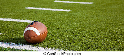 An American football on field - A American football on a...
