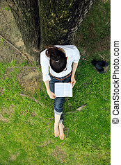 Young woman reading a book in the park - Young student woman...