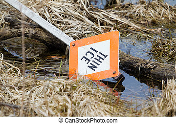 Thin Ice sign laying in a lake