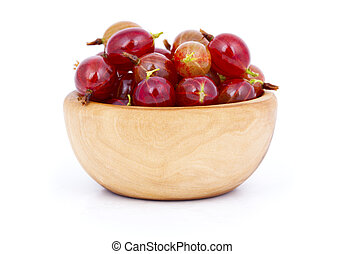fresh red gooseberries in a wooden bowl, over a white...