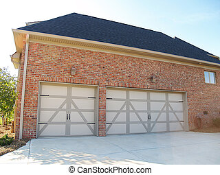 Three Car Garage - Two garage doors on the side of a modern...