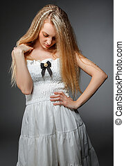 Portrait of the beauty young blond girl in white dress