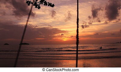 Sea swing Koh Chang. - The boy on a swing. The sunset as a...