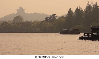 Boats lake Chinese pagoda - Boats go on the lake with...