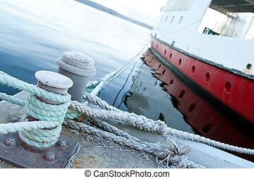 Ship moored at a quay, focus on mooring lines.