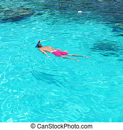 Man snorkeling in crystal clear turquoise water at tropical...