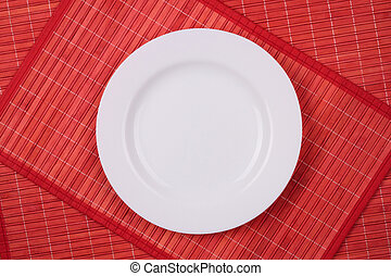 White empty plate on a red