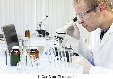 Male Scientist or Doctor Using Laboratory Microscope - A...