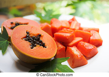 papaya - sweet papaya on the dish with green papaya leaf