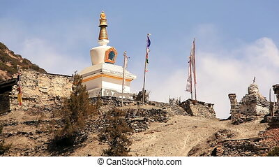 Buddhist Stupa in Himalayas. Flags flutter on a wind.
