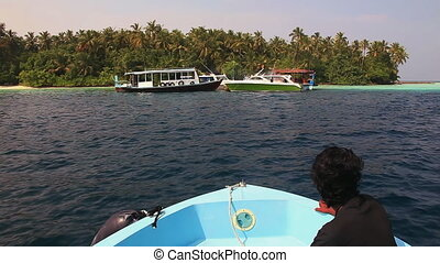 Maldives Boat Island - Motor boat slowly slides on a...
