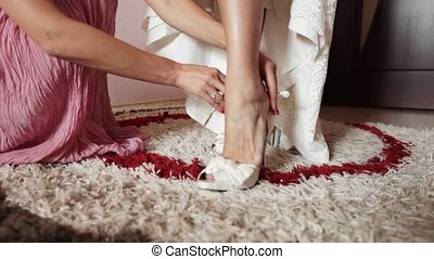 Wedding Shoes - Bridesmaid helps in getting dressed wedding...