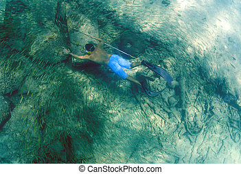 man spearfishing with spear pole underwater in bahamas