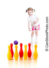 Kid girl throwing ball to knock down toy bowling pins Focus...