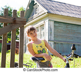 Girl with a bicycle against a village house - Girl with a...