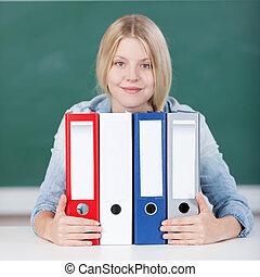 Female Student With Colorful Binders At Desk In Classroom -...
