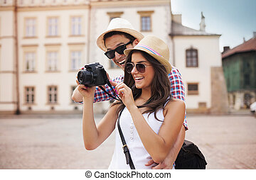 Cute couple looking on their photos on camera