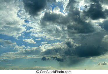 stormy clouds over a sunny sky - Dark grey clouds are...