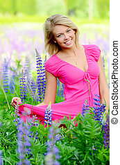 The beautiful woman in the field with lupin - The beautiful...