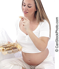 Pregnant woman in bed eating chocolate smiling