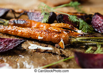 roasted baby carrots and beets with sour cream, close up