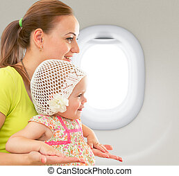 Happy mother and child sitting together in airplane cabin...