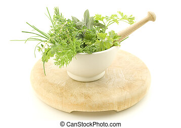 Herbs in Mortar with Pestle - A selection of herbs inside a...