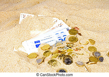 Euro notes and coins in the sand