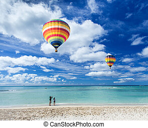 Colorful hot air balloon over Waikiki beach with blue sky...