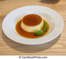 Delicious pudding with caramel and mint leaves On a white...