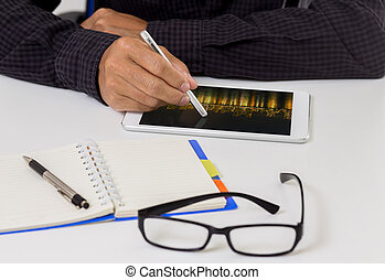 Man hand with stylus pen on modern digital tablet pc at the workplace